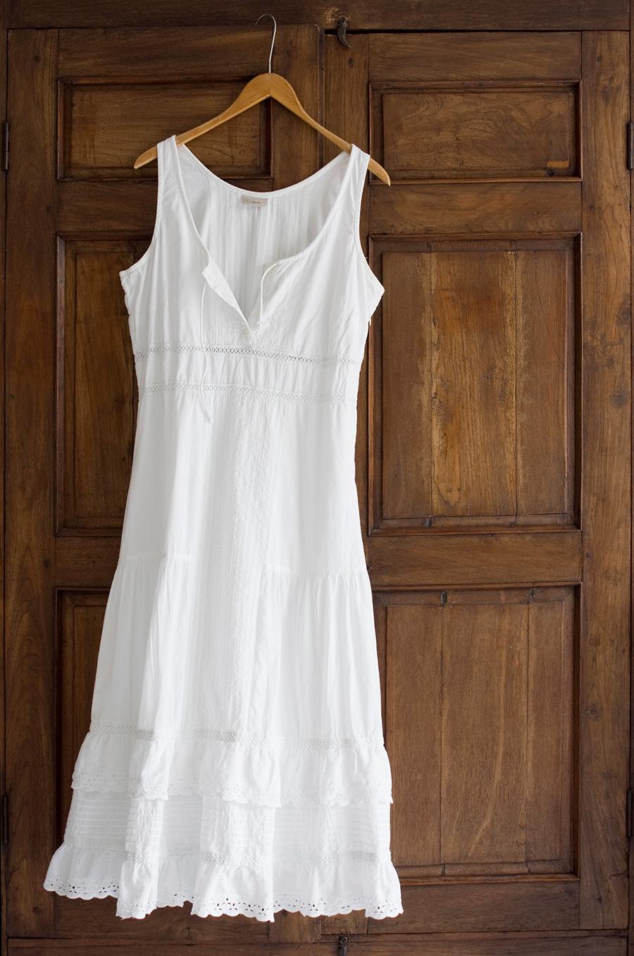 Biała sukienka na lato zawieszona na drzwiach
