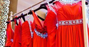 Eleganckie czerwone sukienki na wieszakach w sklepie