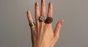 Pierścionki o różnym rozmiarze, kształcie i kolorze na palcach kobiecej dłoni