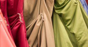 Fragment trzech sukienek - białej, beżowej i zielonej